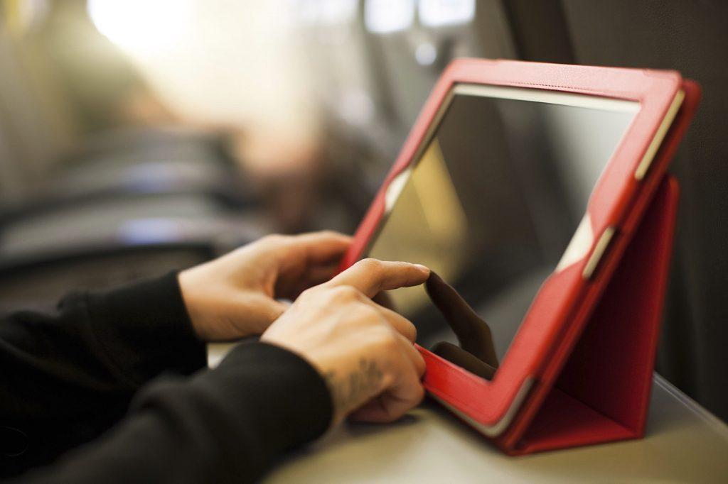 Woman using tablet in airplane during flight