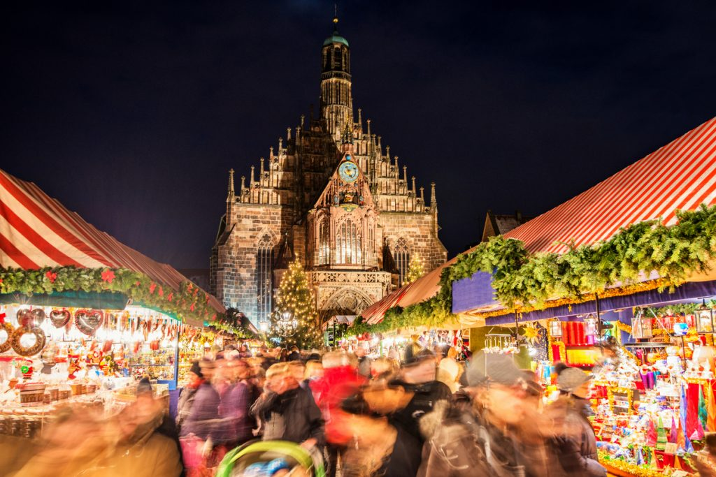 Huge crowd of people moving over Nuremberg´s world-famous christmas market (Christkindlsmarkt) at night, passing colorful illuminated christmas decoration and food stalls. Nuremberg´s landmark Frauenkirche (Church of our Lady) can be seen in the back.