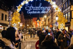 Strasbourg, France - November 28, 2015: Busy Christmas Market Christkindlmarkt in the city of Strasbourg, Alsace region,  France with people photographing the entrance to Christmas Market