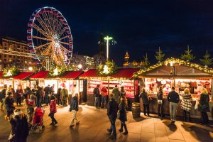 Edinburgh, UK - November 24, 2014: People visiting the Christmas markets in Edinburgh's city centre, with attractions along Princes Street visible in the distance.